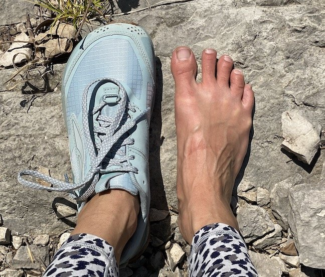 A woman's feet outside on a rock, the left foot is wearing minimalist trail running shoe, the Lone Peak by Altra. The right foot is barefoot.