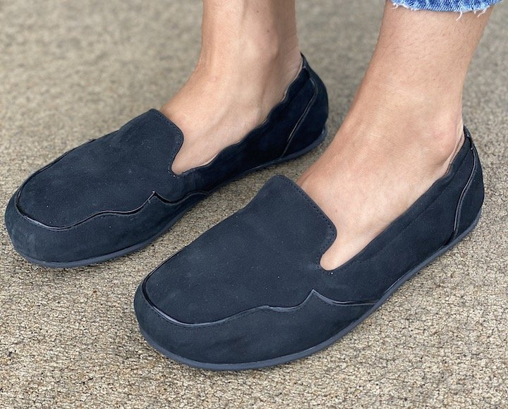 Top side angled photo of a woman's feet in Lisbeth Joe London black suede barefoot loafers with decorative piping to disguise width.