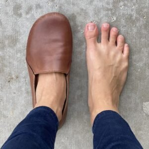 A top down view of a woman's feet with one foot in FeetSutra Khussa barefoot loafers. There is extra space all over the sides and top.