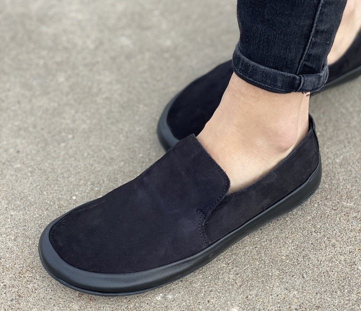A front angled view of Vivobarefoot Opanka Black leather super soft and flexible barefoot loafers.