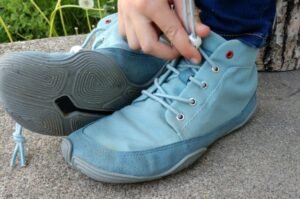 Close up of Wildling Pegasus being put on by a child. The gray outsole on one shoe is visible and the other elastic laces are being cinched.