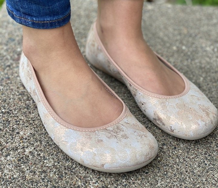 Close up of a woman's extra wide feet in Groundies Bella ballet flats in rose gold