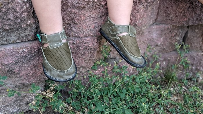 Magical Shoes Bebe on wide toddler feet. The child's feet are in front of a red stone wall