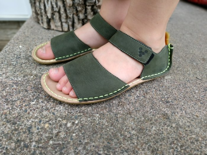 Side angled view of Vivobarefoot Ababa leather kids sandals being worn by a young child.