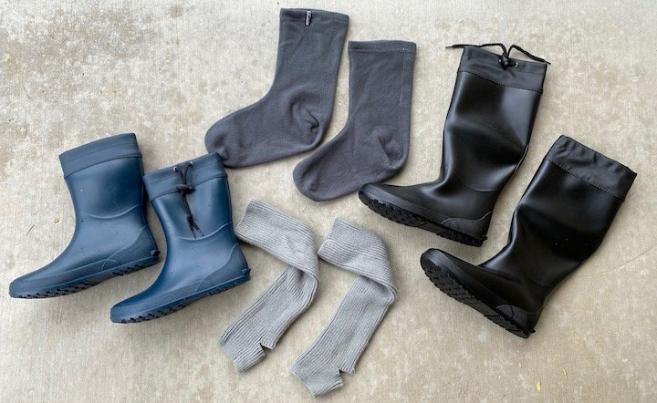 Asgard rain boots on their side with yoga socks and liners laid out with them
