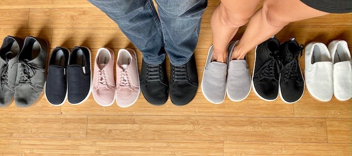 top down view of a man and woman standing in Feelgrounds sneakers amongst a row of 7 pairs of Feelgrounds vegan barefoot shoes