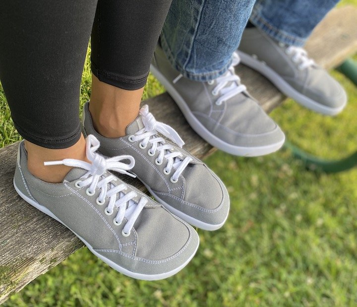 Splay Freestyle affordable athletic sneakers being worn by a man and woman standing on a bench.