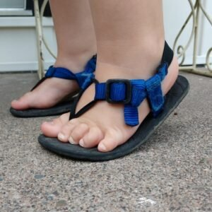 A toddler flexing their feet in Unshoes Keota sandals to show the easy flexibility of these barefoot sandals
